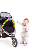 Happy baby and stroller. One year old red haired baby girl with baby stroller. Studio Shot. All toys visible on the photo are officially property released royalty free stock images