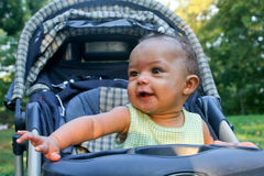 Happy baby in stroller. Young baby girl enjoying ride in her stroller Royalty Free Stock Image