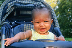 Happy baby in stroller. Young baby girl enjoying ride in her stroller Stock Photo