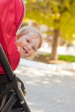 Happy baby in a stroller. Looks out laughing in the park royalty free stock photos