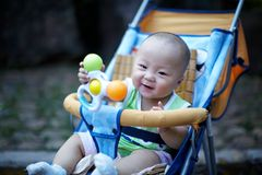 Happy baby in stroller playing toy Royalty Free Stock Photo