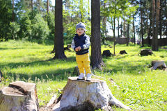 Happy baby on stub in forest Stock Image