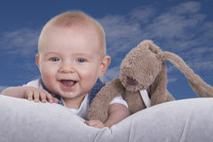 Happy baby with stuffed animal against blue sky Stock Photography