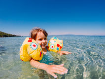 Happy baby swimming. Happy baby girl swimming in sea water stock image