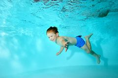 Happy baby swims underwater in the pool and laughs. Portrait. Horizontal view Royalty Free Stock Photography