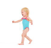 Happy baby in swimsuit running on white Stock Photo
