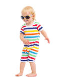 Happy baby in swimsuit and sunglasses dancing Stock Photos