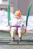 Happy baby in a swing on a sunny winter day Royalty Free Stock Image