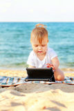 Happy baby with tablet pc on beach. Royalty Free Stock Image