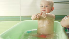 Happy baby taking a bath playing with foam bubbles. Mother washing little boy. Young child in a bathtub. Smiling kids in stock footage