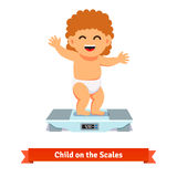 Happy baby toddler in diaper weighting on a scales Stock Image