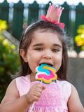 Happy baby toddler girl eating and biting a large colorful lollipop dressed in pink dress as princess or queen with crown. Playing outdoor in garden royalty free stock images