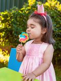 Happy baby toddler girl smelling and savoring a large colorful lollipop smell, scent or aroma. Dressed in pink dress as princess or queen with crown Stock Photo