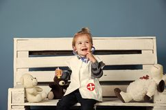 Happy baby with toy pets sit on wooden bench. Happy baby in vet doctor uniform with toy pets sit on wooden bench on blue background. Health, healthcare, medicine Stock Image