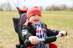 Happy baby on tricycle Stock Images