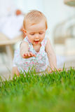 Happy baby trying to touch grass Stock Photo