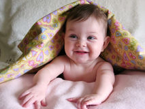 Happy baby under blanket. Beautiful naked baby smiling and looking out from under blanket Stock Photography