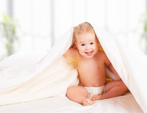 Happy baby under a blanket laughing Stock Photo