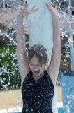 Cheerful girl at the fountain in the water park Stock Images