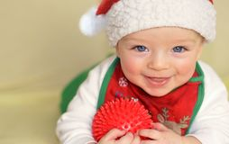 Happy baby wearing Christmas bib and cap Stock Photos