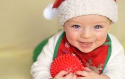 Happy baby wearing Christmas bib and cap Stock Photos