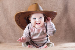 Happy baby wearing cow girl outfit with big hat Royalty Free Stock Image