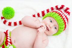 Happy Baby Wearing Cute Knit Hat. Baby wearing red white and green striped knit hat Royalty Free Stock Image
