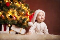 Happy baby wearing Santa hat over christmas tree Stock Photos