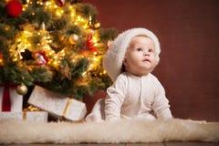 Happy baby wearing Santa hat over christmas tree Royalty Free Stock Image