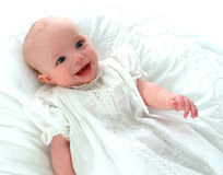 Happy Baby in White Dress. Smiling baby girl in white dress on white background Stock Photos