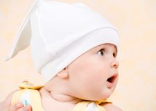 Happy baby in a white hat looking up Stock Image