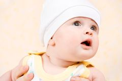 Happy baby in a white hat looking up Royalty Free Stock Image