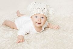 Happy Baby in White Knitted Hat Crawling on White Blanket. Infant Kid Boy Portrait, Smiling Child six months old royalty free stock image