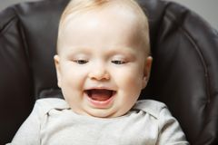 Happy baby with wide open mouth portrait photo. Happy baby with wide open mouth sits in chair and looks down portrait photo. Charming little kid with blond hair Royalty Free Stock Photos