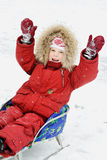 Happy baby in winter clothing on sledge Stock Images