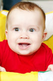 Happy baby in a yellow buggy. Happy baby age of 7 months in a yellow baby carriage royalty free stock images