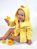 Happy Baby in Yellow Duck Robe. A baby girl in a yellow duck bathrobe holds a plastic toy rubber duck royalty free stock image