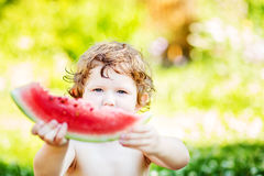 Happy babyl eating watermelon  in summer park Stock Images