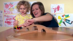 Happy babysitter and toddler child girl play with wooden train in kindergarten stock video footage