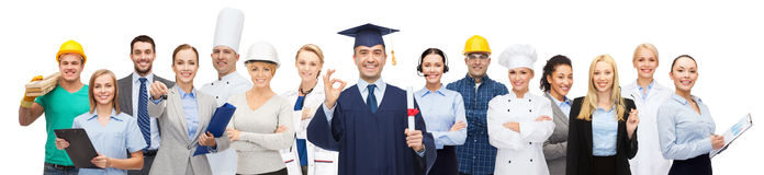Happy bachelor with diploma over professionals. People, profession, education, gesture and success concept - happy bachelor with diploma showing ok sign over Royalty Free Stock Photography