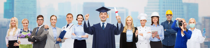 Happy bachelor with diploma over professionals Royalty Free Stock Photography