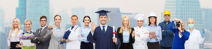Happy bachelor with diploma over professionals Stock Photo