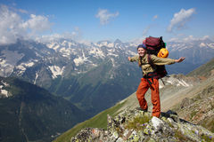 Happy backpacker girl in a mountains stock photo