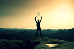 Happy backpacker with x crossed poles in the air, open misty mountain valley bellow cliff. Silhouette of tourist Royalty Free Stock Image