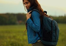 Happy backpacking adventurous woman have a trip with blue huge h. Aversack on nature summer background stock photo