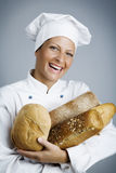 Happy baker. Female baker with hands full of bread royalty free stock photo