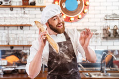 Happy baker holding loaf of bread and showing ok sign Stock Images