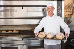 Happy baker holding tray of fresh bread Stock Image