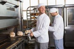 Happy baker holding tray of fresh bread Stock Photography