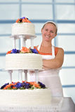 Happy Baker Lady smiling infront of her Ruffled Wedding Cake Royalty Free Stock Photography